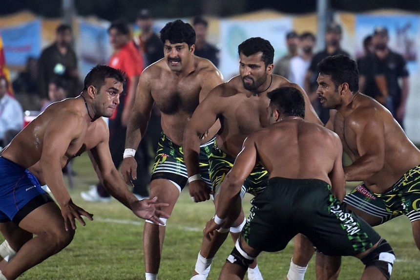 An Indian kabaddi player (left) attempting to tag a Pakistani opponent during the 3rd Asian Kabaddi Circle Style Championship on May 6, 2016.