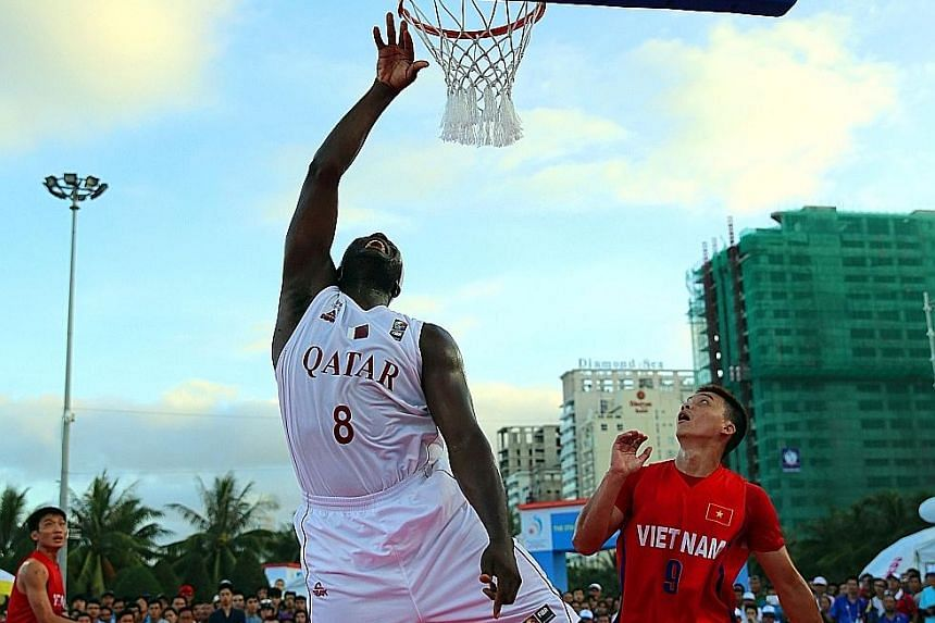 Qatar (in white) taking on Vietnam (in red) in a men's 3-on-3 basketball match at the Asian Beach Games in Vietnam's central coastal city of Danang. Qatar won gold after beating Mongolia in the final.