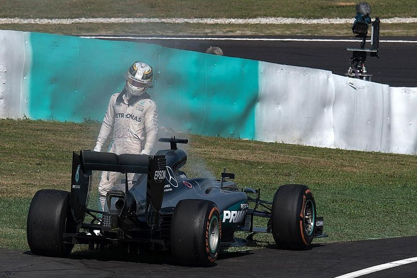 Lewis Hamilton leaving his car after flames appeared at the back of his Mercedes following engine failure during the Malaysia Grand Prix.