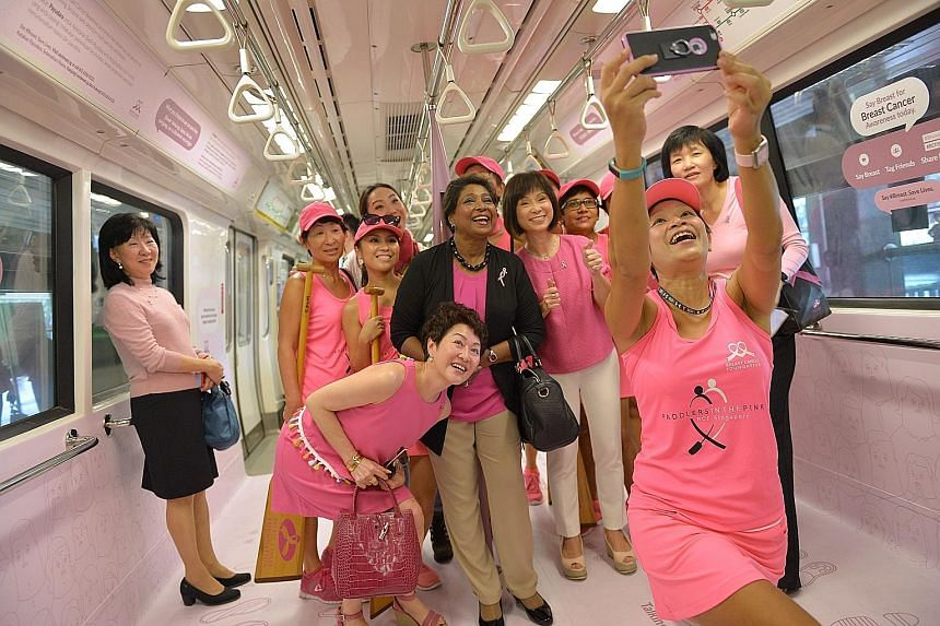 "Senior Minister of State for Health Amy Khor (fourth from right), and BCF president Noor Quek (in black jacket) at the launch of the ""pink"" train yesterday. The train features statistics about breast cancer and will also include social ""nudges"" to en"