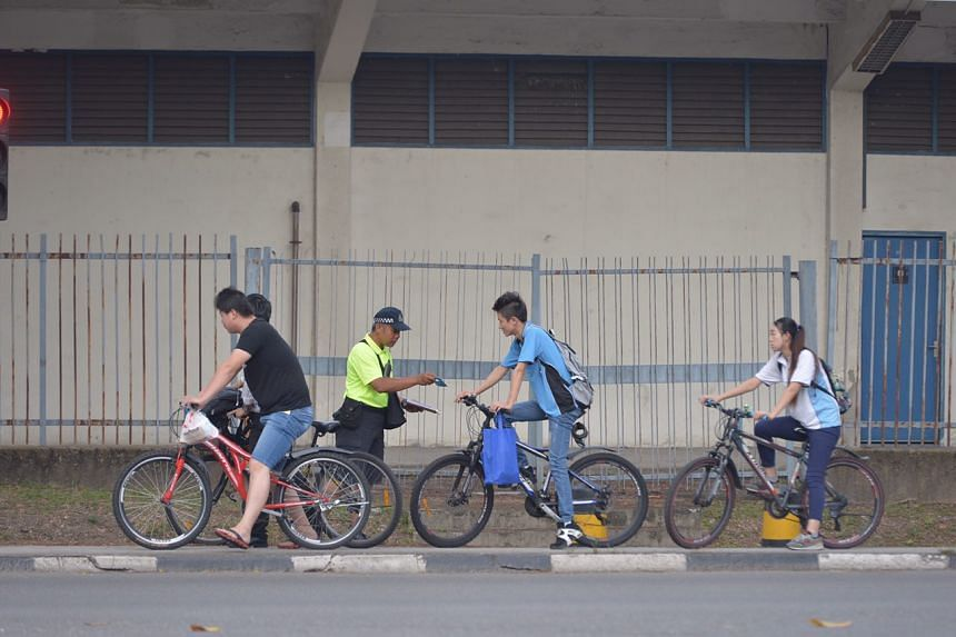 LTA enforcement officer giving out brochures to cyclists.