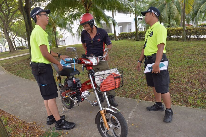 LTA enforcement officers checking for illegally modified e-bikes.