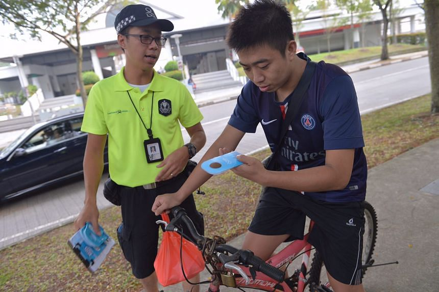 LTA enforcement officer giving out a brochure to a cyclist.