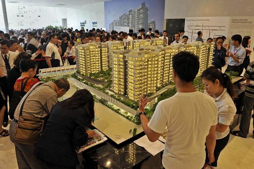 Prospective buyers and property agents checking out the list of units at a condominium showflat.