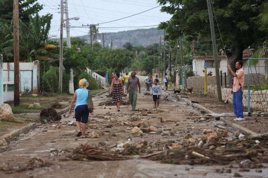 People walk on the street after strong waves hit the coast at Siboney beach ahead of the arrival of Hurricane Matthew in Cuba, Oct 4, 2016.