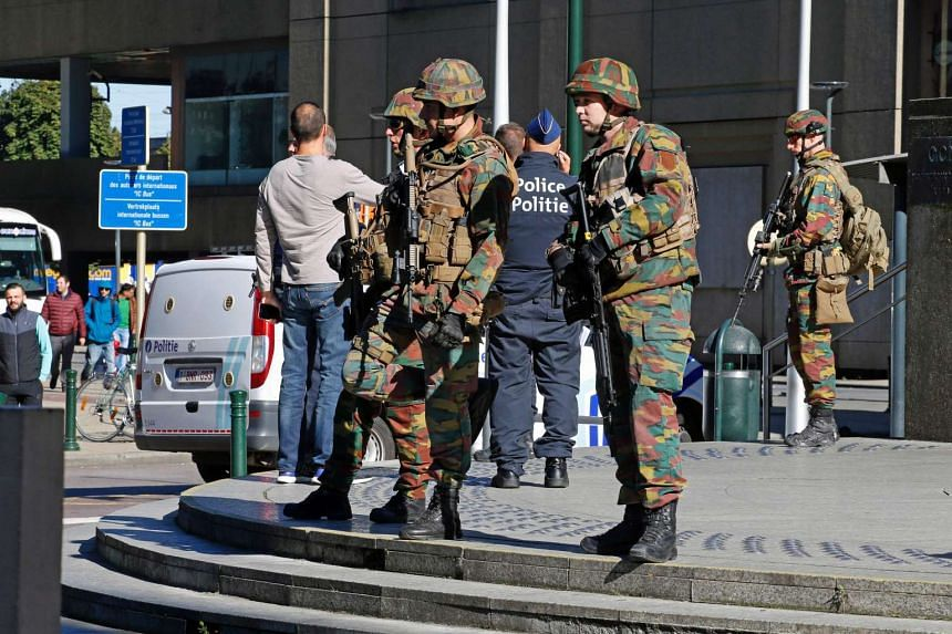 Police and army personnel standing guard during a bomb alert outside the Brussels-North (Gare du Nord - Noordstation) train station in Brussels, on Oct 5, 2016.