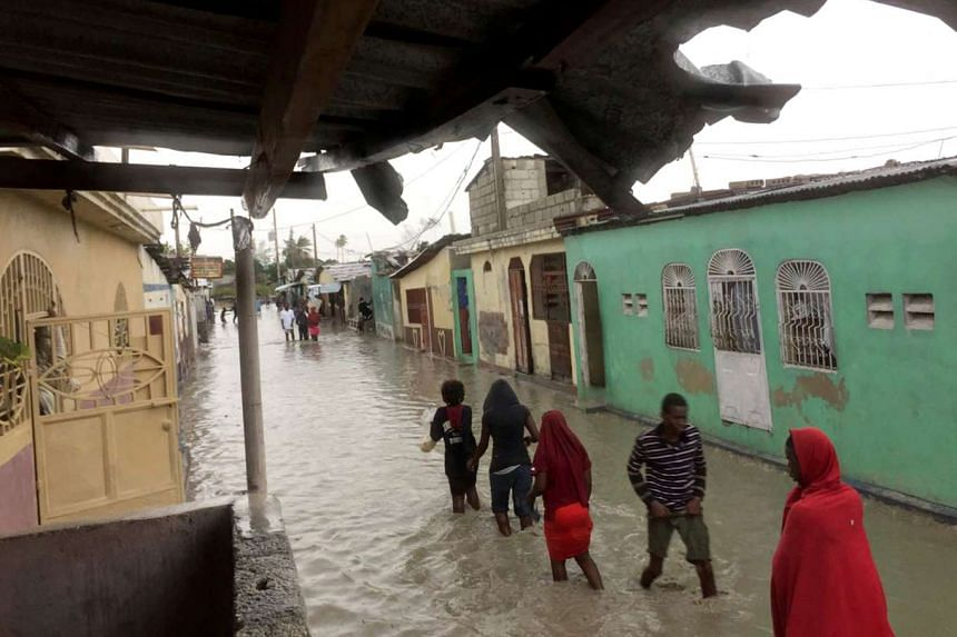 People wade through a flooded street while Hurricane Matthew passes, in Cite-Soleil in Port-au-Prince, Haiti, Oct 4, 2016.