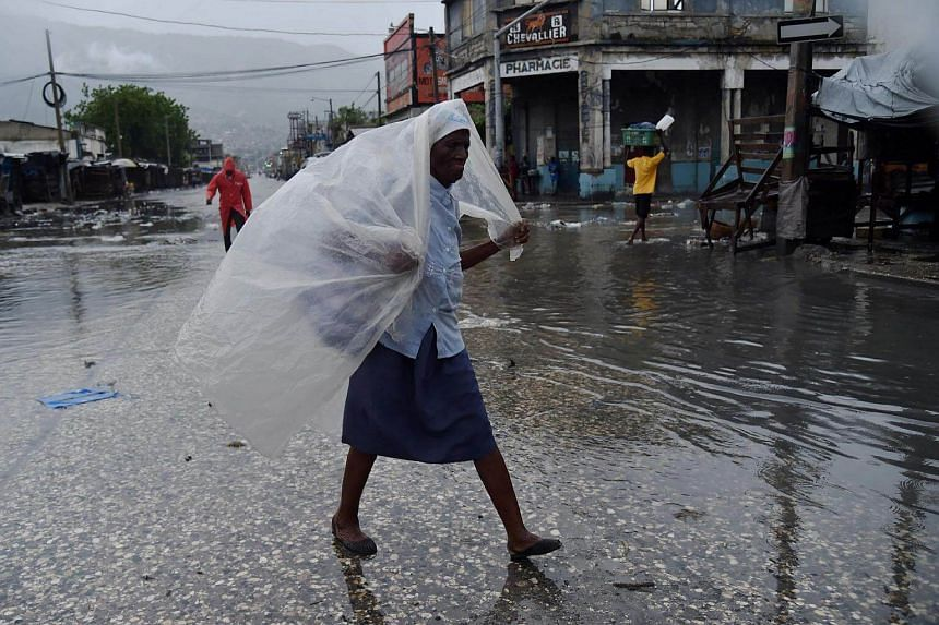 A woman protecting herself from the rain with plastic after hurricane Matthew, in Port-au-Prince, on Oct 4, 2016.