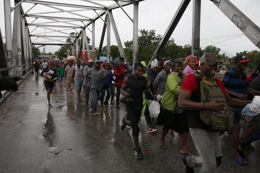 People crossing a bridge over a rushing river as part of evacuations during Hurricane Matthew in Port au Prince, Haiti, on Oct 4 2016.