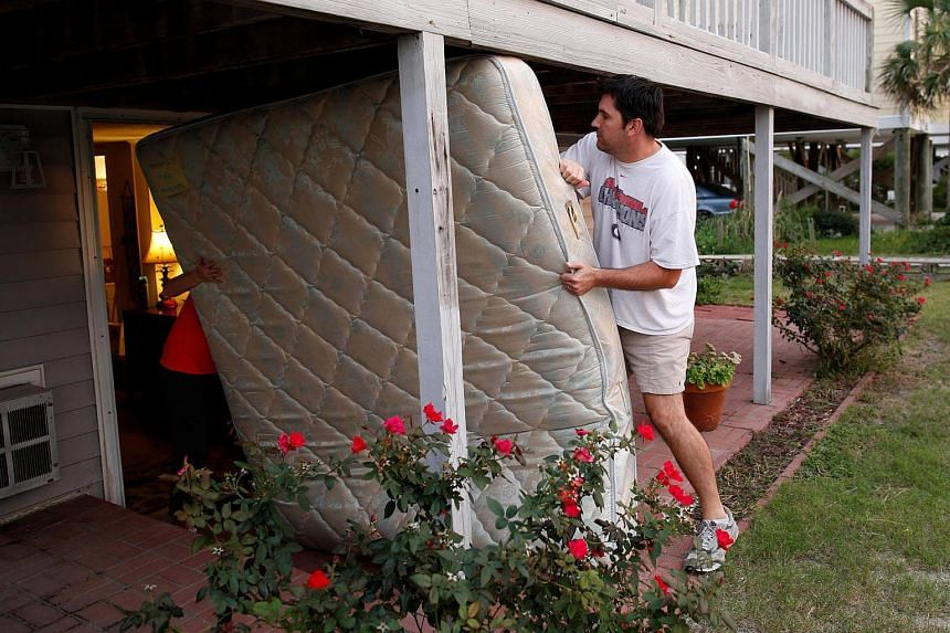 Dean Legge (right) helping his sister-law Josey Vereen (left) remove a mattress at her beachfront home along Waccamaw Drive in anticipation of Hurricane Matthew in Garden City Beach, South Carolina, US, on Oct 4 2016.