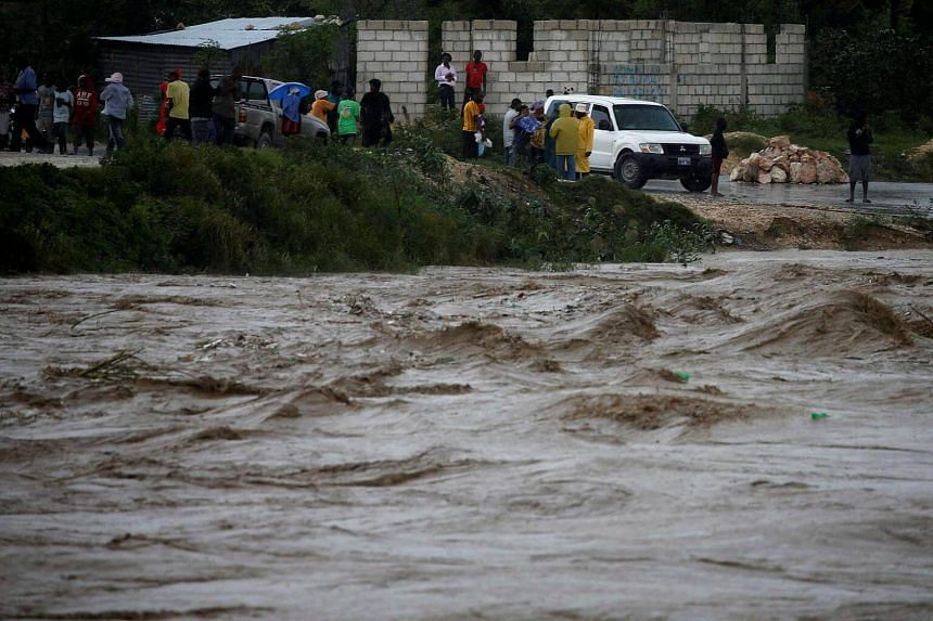 People inspecting the rising water level of a river due to the rains caused by Hurricane Matthew passing through Port-au-Prince, Haiti, on Oct 4 2016.