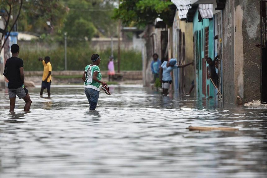 People are seen walking in flooded streets, in a neighbourhood of the commune of Cite Soleil, in the Haitian Capital Port-au-Prince, on Oct 4, 2016.
