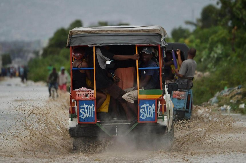 A car making its way through flooded street, in a neighbourhood of the commune of Cite Soleil, in the Haitian Capital Port-au-Prince, on Oct 4, 2016.