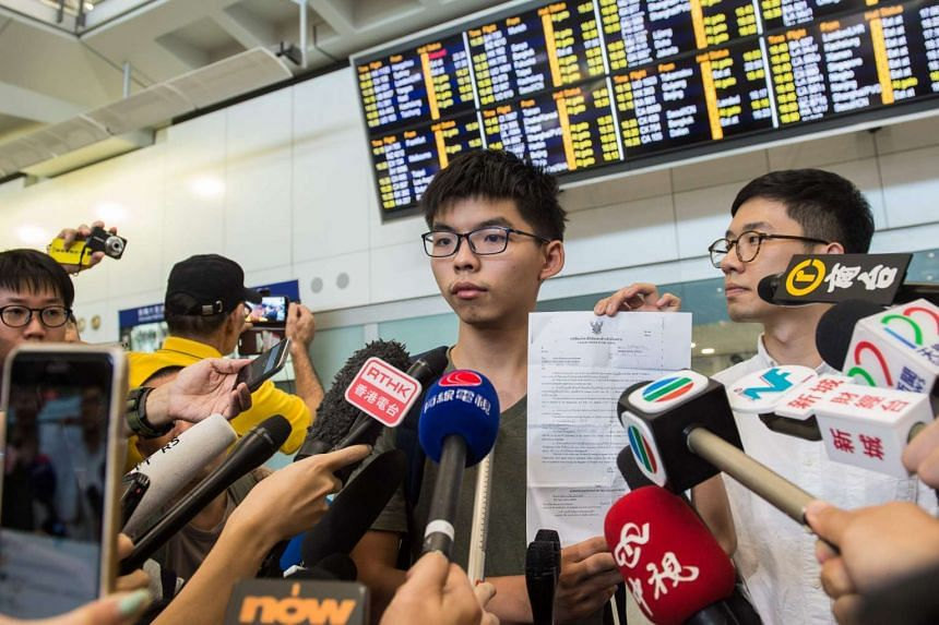 Hong Kong democracy campaigner Joshua Wong (centre) holds up his expulsion order from Thai authorities during a press conference upon his arrival at the international airport in Hong Kong on Oct 5, 2016.