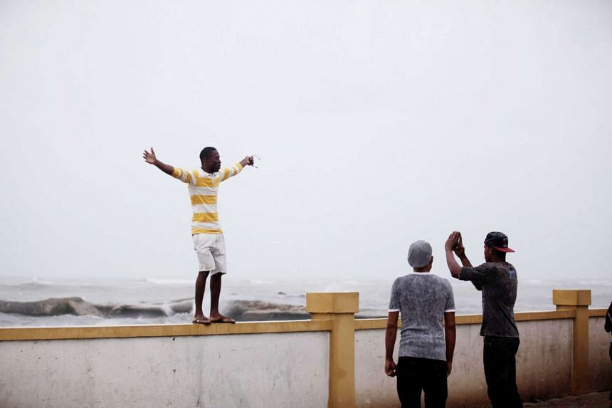 A man posing for a picture beside the sea before Hurricane Matthew battered Haiti. More than 6,400 people have been evacuated to temporary shelters. Forecasts say landslides are likely before the storm moves on to Cuba.