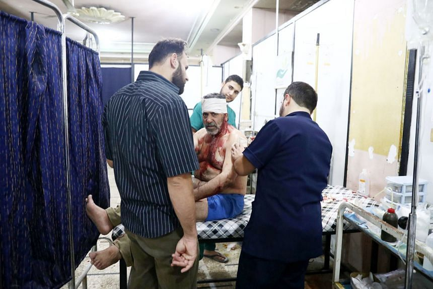 An injured Syrian man receiving treatment at a makeshift hospital on Monday, following reported air strikes in the rebel-held town of Douma, on the eastern outskirts of the capital Damascus.