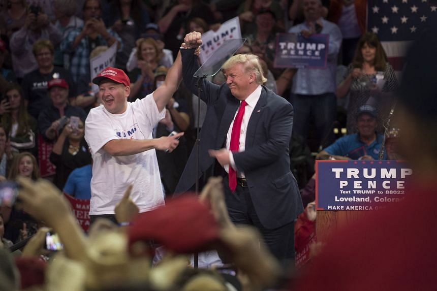 Mr Donald Trump (right) with a man he called on stage to thank for waiting since 4am to attend a rally in Colorado on Monday. A poll shows rival Hillary Clinton leading in the key swing states of Florida, Pennsylvania and North Carolina, but trailing him