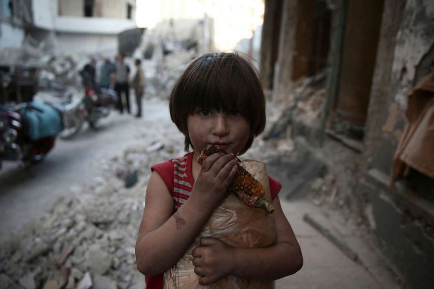 A child eats corn while carrying a bag of bread in an area damaged by an airstrike in the rebel-held Douma neighbourhood of Damascus, Oct 4, 2016.