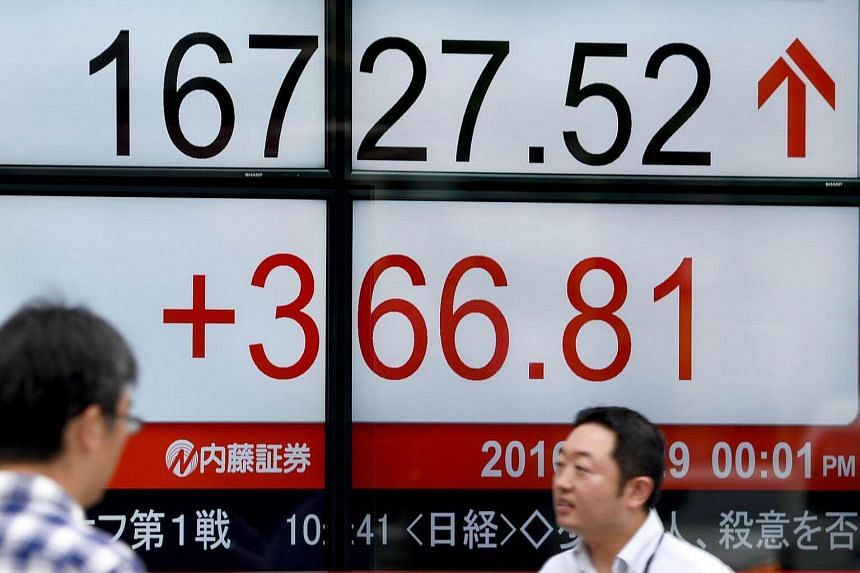 People walk past an electric quotation board flashing the Nikkei key index of the Tokyo Stock Exchange (TSE) in front of a securities company in Tokyo.