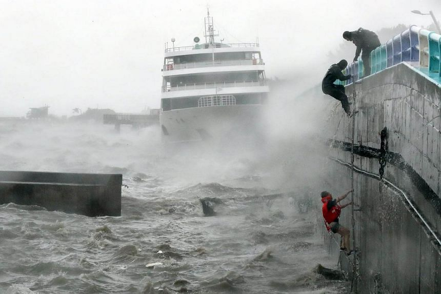Crew members of a passenger boat stranded during Typhoon Chaba are rescued in Yeosu, South Korea.