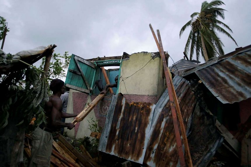 Men working amid the wreckage of a house destroyed by Hurricane Matthew in Les Cayes, Haiti, on Oct 5, 2016.
