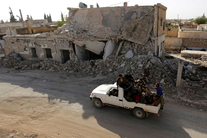 Rebel fighters ride past damaged buildings in the northern Syrian rebel-held town of al-Rai, in Aleppo on Oct 5, 2016.