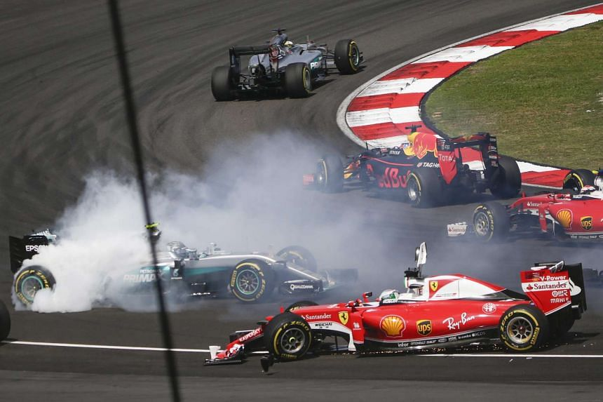 Sebastian Vettel (right) of Ferrari and Nico Rosberg (left) of Mercedes collide on the first corner during the start of the Malaysian Formula One Grand Prix in Sepang on Oct 2, 2016.