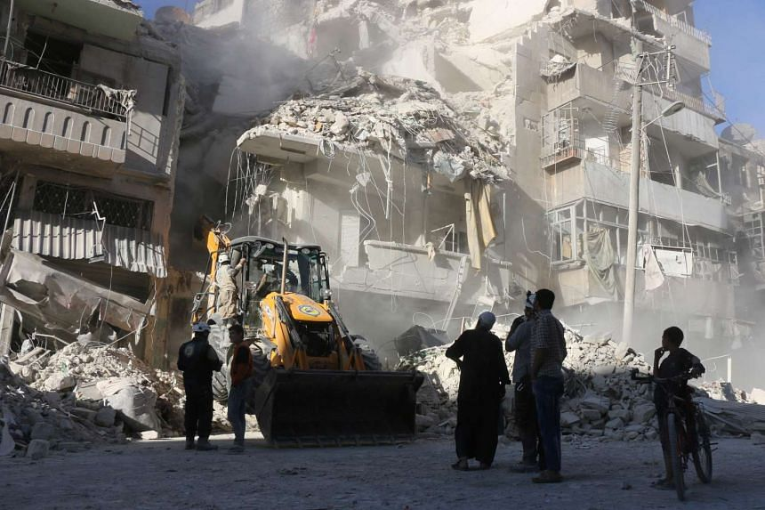 Civilians watch as a tractor clears the rubble following Syrian government forces airstrikes in the rebel held neighbourhood of Tariq a-Bab in Aleppo on Sept 24, 2016.