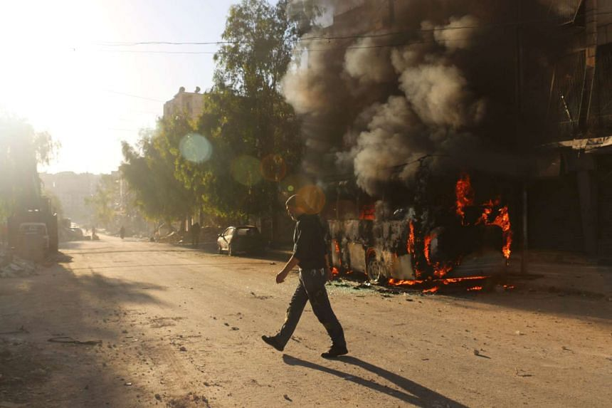 A Syrian man walks past a bus set ablaze following a reported air strike in the rebel-held Salaheddin district of Aleppo on Sept 25, 2016.