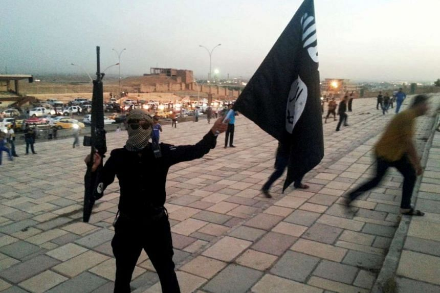 A fighter of the Islamic State of Iraq and and Syria (ISIS) holds an ISIS flag and a weapon on a street in the city of Mosul, Iraq June 23, 2014.