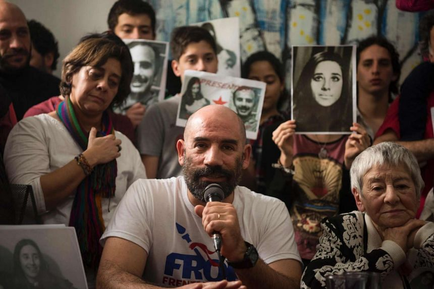 Ramiro Menna (centre), brother of the 121st grandson found by the Abuelas of the Plaza de Mayo (Grandmothers of Plaza de Mayo) humanitarian organisation speaks next to his aunt Alma Lanzillotto, during a press conference in Buenos Aires, on Oct 5, 20