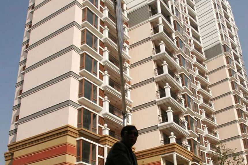 A cyclist passes by the Pearl River Garden complex, a European-style development in northeast Shanghai, on Nov 28, 2005.