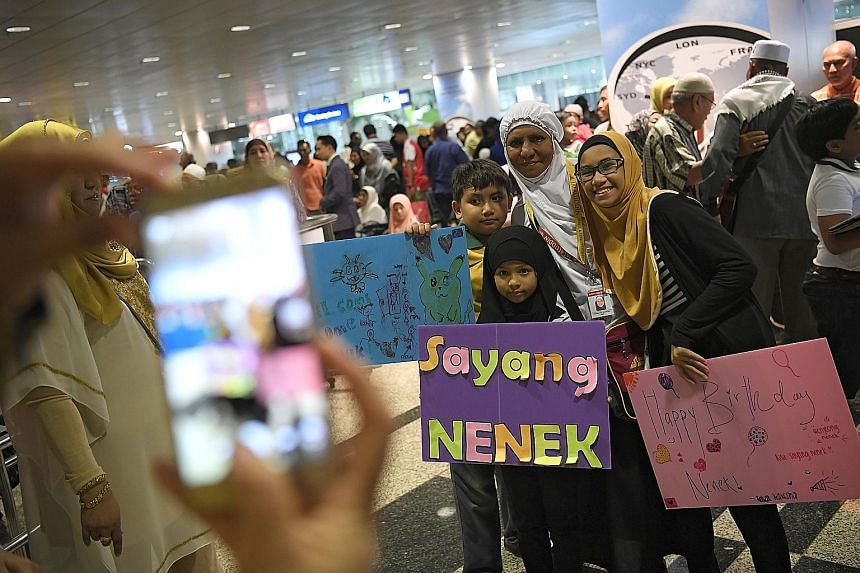 Three siblings turned up at Changi Airport yesterday to greet their grandmother, housewife Azizah Sawal (in white tudung), who was returning from the haj in Mecca. Yesterday was her 57th birthday, and her grandchildren (from left) Hadi Danial, nine,