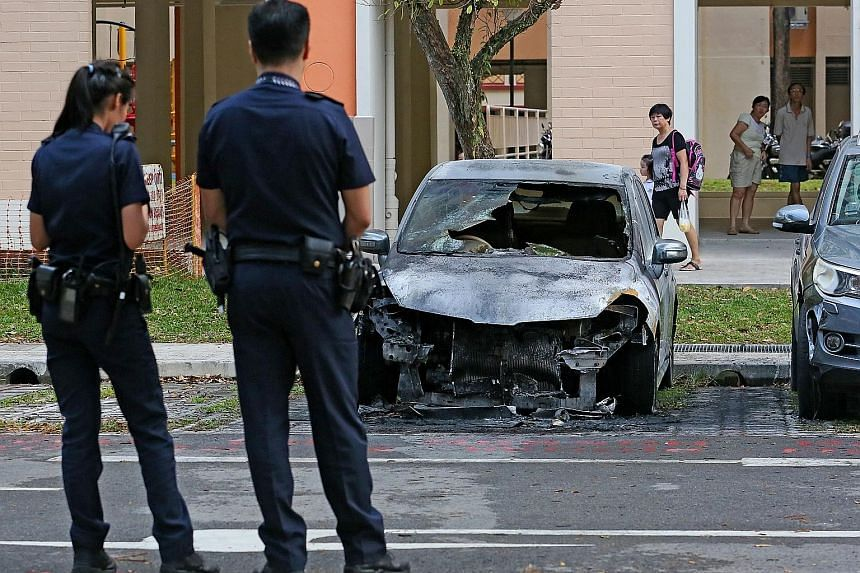 The car in the Ang Mo Kio carpark is reduced to a blackened heap. A fire broke out in its engine compartment on Tuesday afternoon. Residents nearby said they heard loud bangs as the car burned.