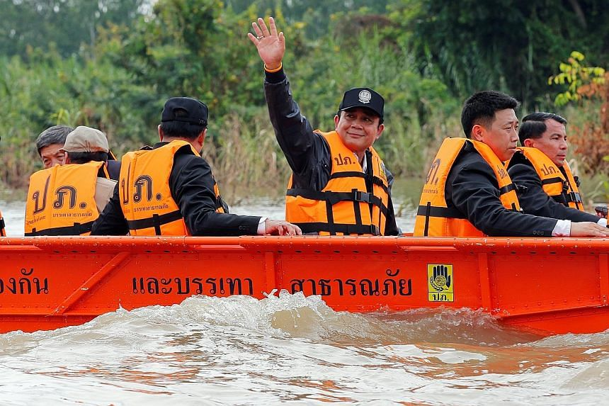 Thailand's Prime Minister Prayuth Chan-o-cha waves to flood-affected residents during his visit to Sena district in the ancient city of Ayutthaya yesterday. Floods in the past few weeks, and an overflow of water from the Chao Phraya river, have inund