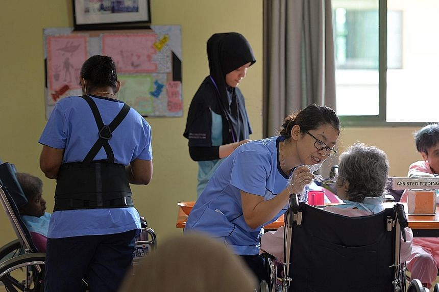 Nursing aide Nyein Pyae Sone (right), 34, feeding a resident at Jamiyah Nursing Home. Some 85 per cent of the home's care staff are foreigners, mainly from the Philippines, Myanmar and India.