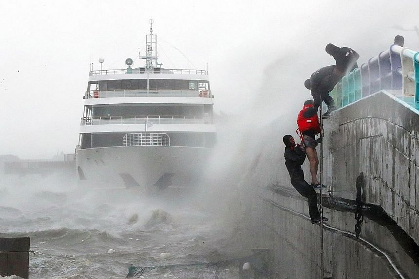 South Korean coast guard personnel rescuing crew members of a stranded passenger ship in the aftermath of Typhoon Chaba in the southern city of Yeosu yesterday. Chaba has killed at least four people as it bulldozed through southern parts of South Kor