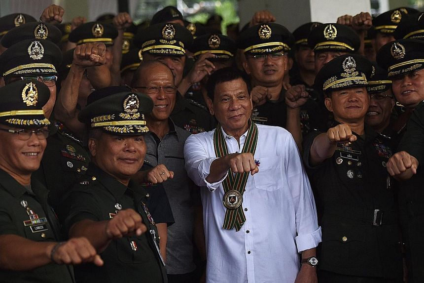 """Mr Duterte (centre) with military officers during a """"talk with the troops"""" session in Manila on Tuesday."""