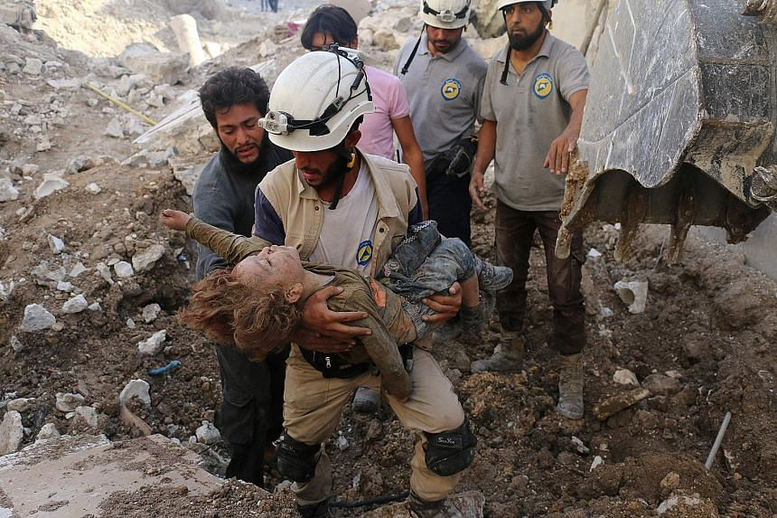 A Syrian civil defence volunteer, from the group known as the White Helmets, holds the body of a child pulled from the rubble following an air strike by government forces on the rebel-held neighbourhood of Karm Homad in the northern city of Aleppo on