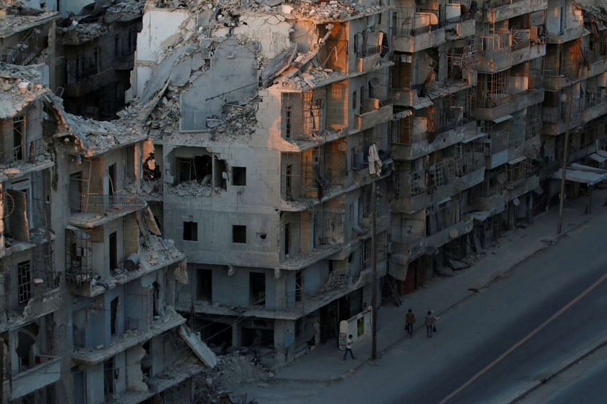 People walk past damaged buildings in the rebel-held Tariq al-Bab neighbourhood of Aleppo, Syria on Oct 5, 2016.