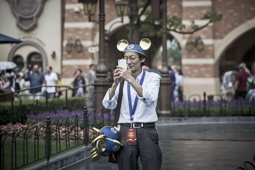 A visitor wearing gold Mickey Mouse ears takes photographs with his smartphone during the opening day of Walt Disney Co.'s Shanghai Disney Resort.