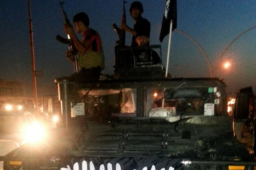 ISIS fighters celebrate on a vehicle in the city of Mosul, Iraq.