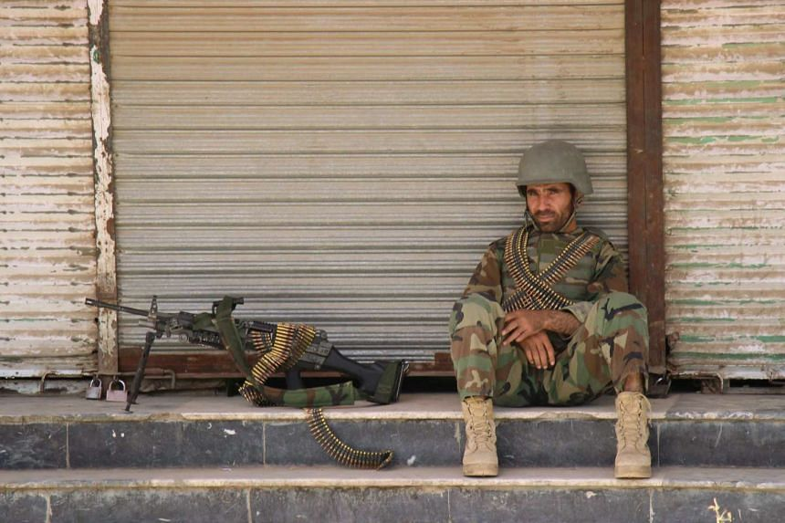 An Afghan National Army soldier sits in front of a closed shop in the downtown of Kunduz city, Afghanistan Oct 3, 2016.