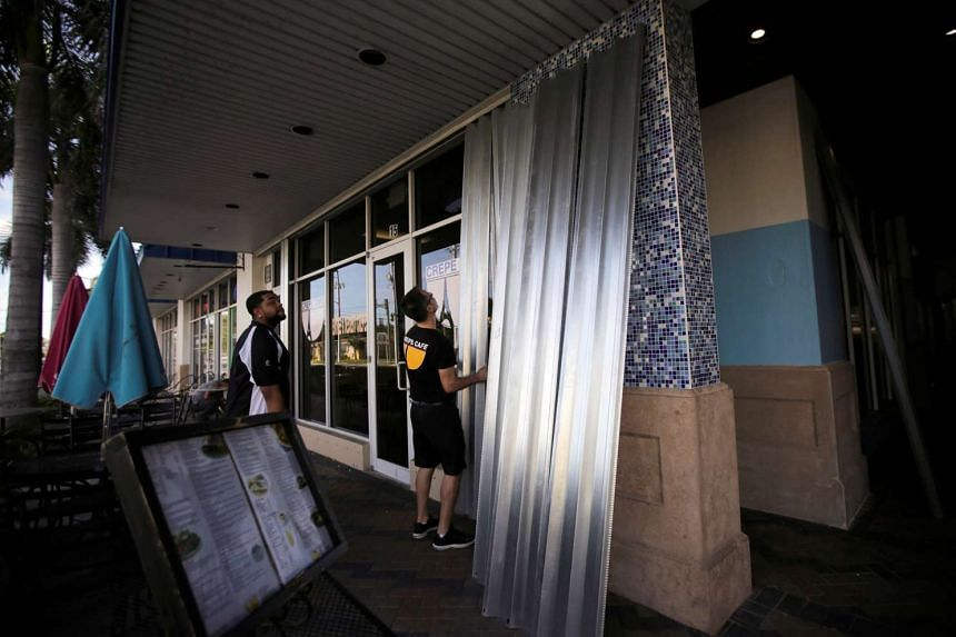 Employees cover the doors and windows at a restaurant in anticipation of Hurricane Matthew in Florida on Oct 5, 2016.