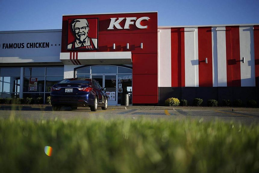 A car sits parked outside of a Yum! Brands Inc. KFC restaurant.