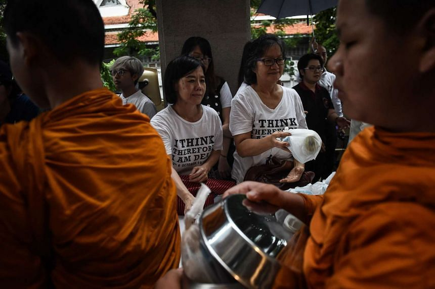 Women give alms to monks in a ceremony to commemorate the 40th anniversary of the Oct 6, 1976 Thammasat University student massacre in Bangkok on Oct 6, 2016.
