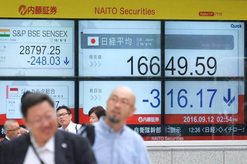 Pedestrians walk past an electric quotation board displaying the Nikkei key index of the Tokyo Stock Exchange in Tokyo.