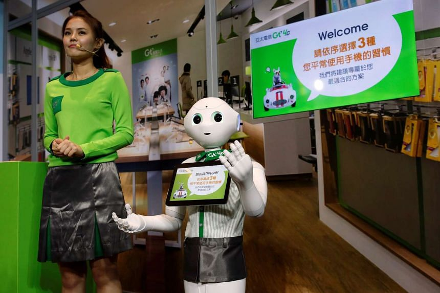 """SoftBank's robot """"Pepper"""" dressed in Asia Pacific Telecom uniform, is displayed during a news conference in Taipei, Taiwan."""