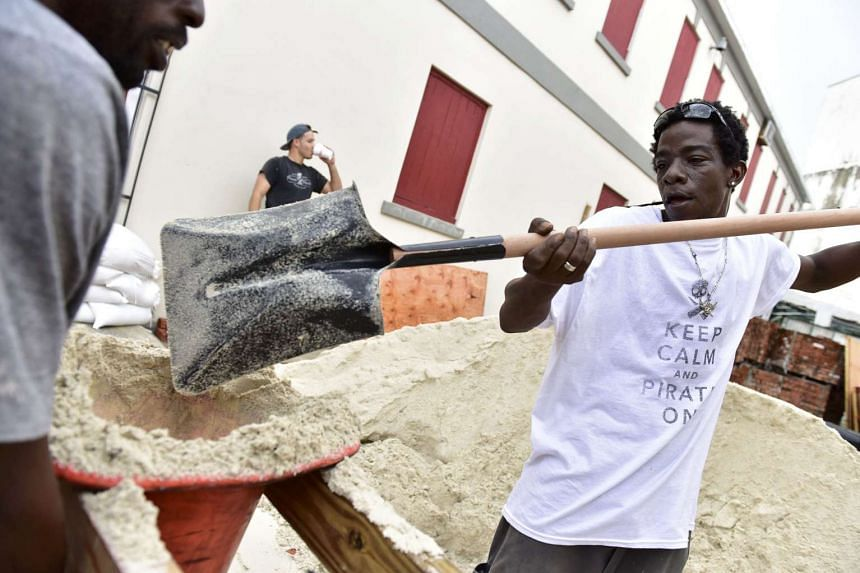Brewery employees work to make sandbags in the heart of downtown as Hurricane Matthew approaches Nassau, Bahamas Oct 5, 2016.