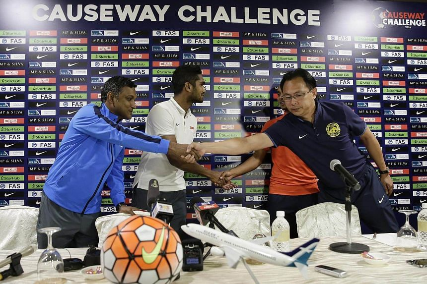 Singapore national team coach V. Sundramoorthy (left) and captain Hariss Harun (second from left) shaking hands with their Malaysian counterparts Ong Kim Swee (right) and Amri Yahyah during the Causeway Challenge press conference.